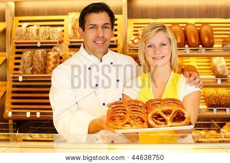 Baker and shopkeeper in a bakery present pretzels
