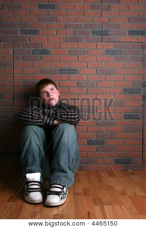 Teenage Boy Sitting Against The Wall With His Knees Up And Arms Crossed