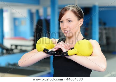 Happy Young Woman Exercising With Kettle Bell Weight
