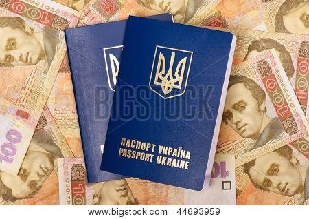 Two international Ukrainian passports on Hryvna banknotes background
