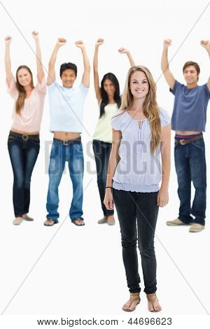Woman smiling with people with their arms raised behind her against white background