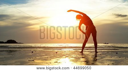 Silhouette young woman, exercise on the beach at sunset. poster