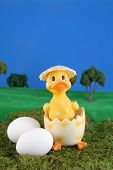 and easter chick in a freshly cracked egg on grass with blue background poster