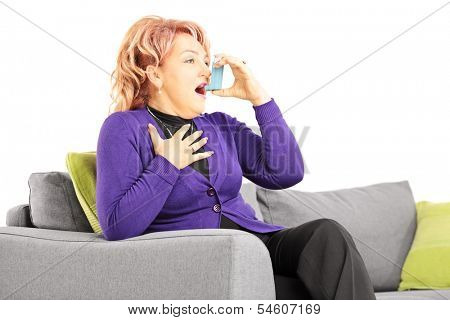 Mature woman seated on a sofa taking asthma treatment with inhaler, isolated on white background
