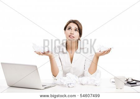 Business woman at the office with the desk full of crumpled papers, isolated over a white background