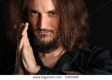 Young Man Praying And Looking At Camera Isolated On Black Background