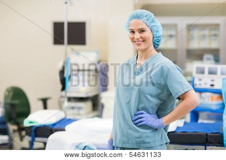 Portrait of beautiful surgeon with hand on hip standing in operation room poster