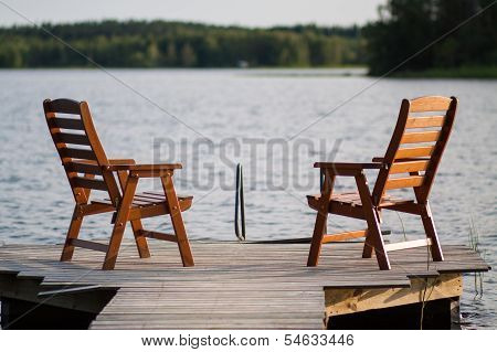Wooden Chairs Sitting On The Dock