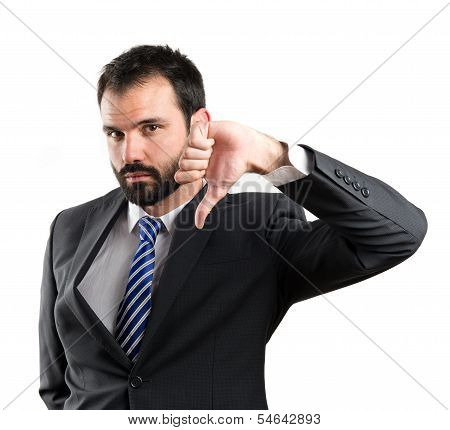 Young Businessman With His Thumb Down Over White Background
