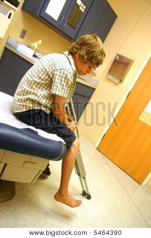 A Boy With Crutches Sits, Awaiting The Doctor