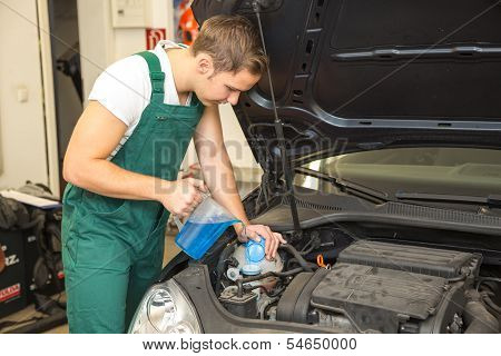 Mechanic refills coolant or cooling fluid in motor of a car poster