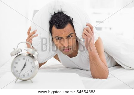 Sleepy young man covering ears with pillow as he looks at alarm clock in bed
