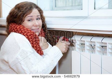 Young Woman Feels Cold When Turning Thermostat Of Central Heating Convector