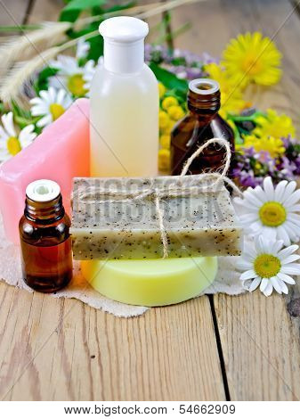 Oil With Lotion And Soap With Wildflowers On The Board