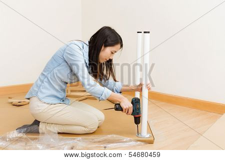 Asian woman using strew driver for assembling furniture