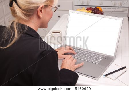 Woman In Kitchen Using Laptop With Blank Screen