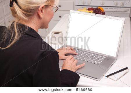 Frau In der Küche mit Laptop mit leerer Bildschirm
