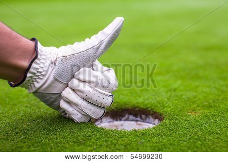 Men's Hand In A Glove Golf Shows Ok Near The Hole