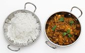 Methi murgh - chicken cooked with fresh fenugreek leaves - in a kadai, or karahi, traditional Indian wok, over white, garnished with fenugreek leaves and seen from above next to a bowl of basmati rice poster