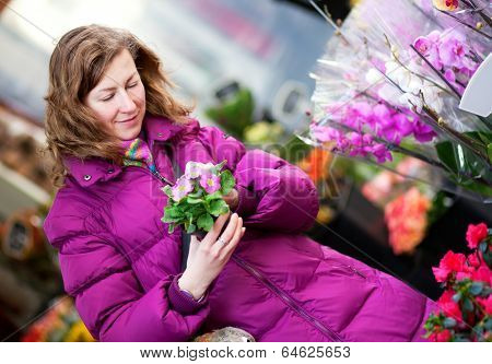 Beautiful Girl In Bright Clothes Choosing Flowers At Market