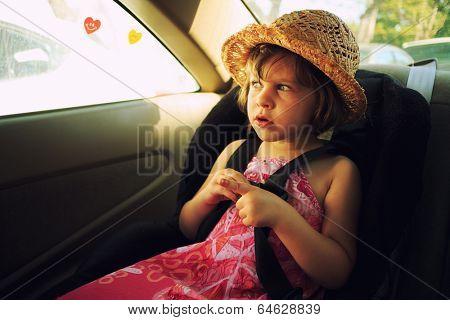 Three year old girl sitting in car seat.