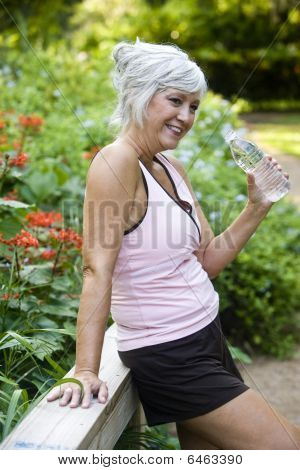 Woman in workout clothes drinking water in park