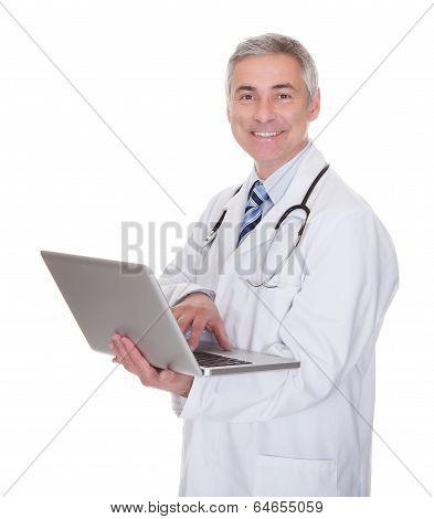 Portrait Of Male Doctor Using Laptop