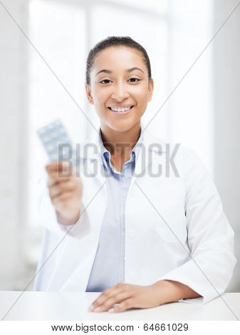 healthcare and medical concept - african doctor with blister packs of pills