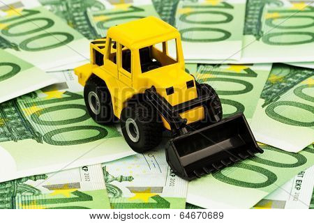 an excavator standing on euro banknotes. symbolic photo for costs, revenues and subsidies in the construction industry and the construction industry