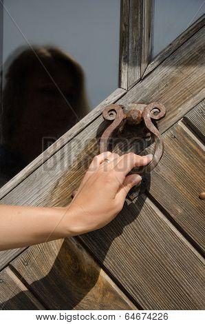 guest hand knock retro rusty metal door handle used as buzzer ringer knocker. poster