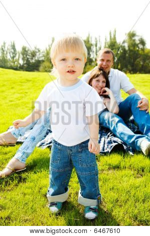 Toddler And Parents On Grass