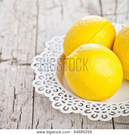 three fresh lemons on rustic wooden background