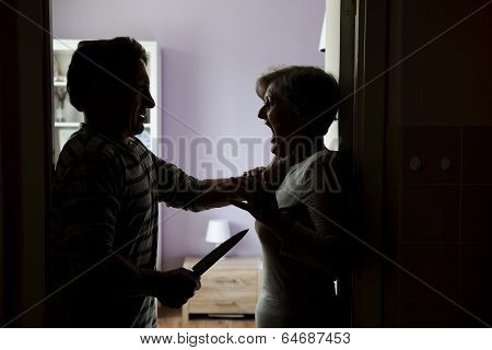 Silhouette of mature couple fighting, the man is attacking woman with knife. Woman is victim of domestic violence poster