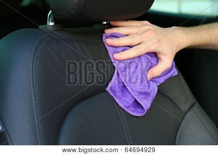 Hand with microfiber cloth polishing car