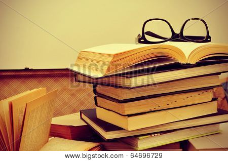 a pile of books and a pair of eyeglasses in an old suitcase, with a retro effect