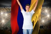 Pretty football fan in white cheering holding colombia flag against vast football stadium with fans in yellow poster
