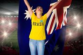 Excited football fan in brasil tshirt holding australia flag against vast football stadium with fans in red poster