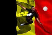 Football player in black kicking against belgium flag poster