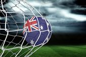 Football in australia colours at back of net against football pitch under stormy sky poster