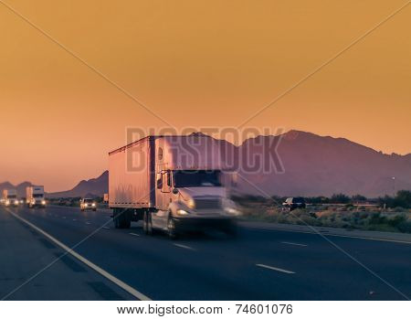 Heavy duty truck lorry traveling on desert highway with mountain background.