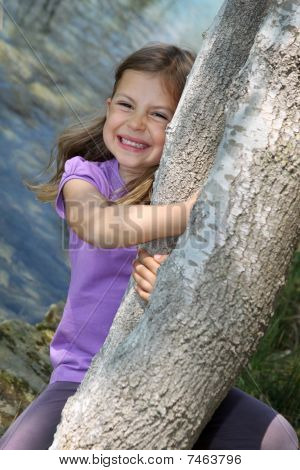 Girl swinging from tree trunk