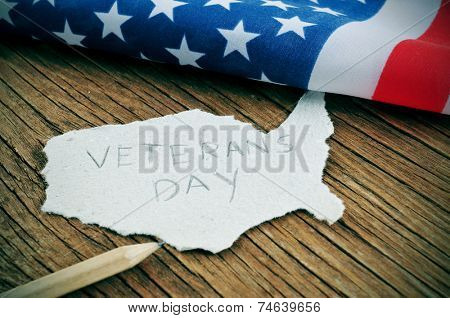 a piece of paper in the shape of United States with the word Veterans Day on a wooden background with the flag of the United States in the background poster