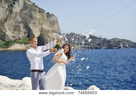 Young Married Couple Uncorking Champagne Bottle By The Sea After Their Wedding