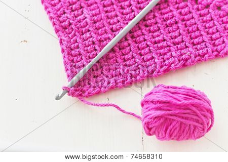Homemade crocheted dishcloth with crochet hook and