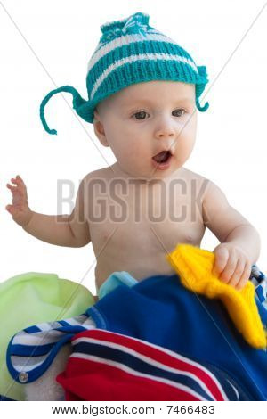 The Baby In A Knitted Cap Sits In A Heap Clothes