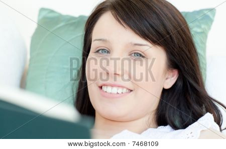 Cheerful Woman Reading A Book Lying On A Sofa