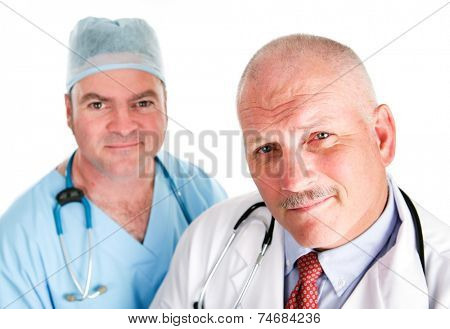 Portrait of mature doctor and younger surgeon isolated on white.