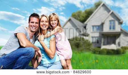 Happy family near new house. Real estate background.