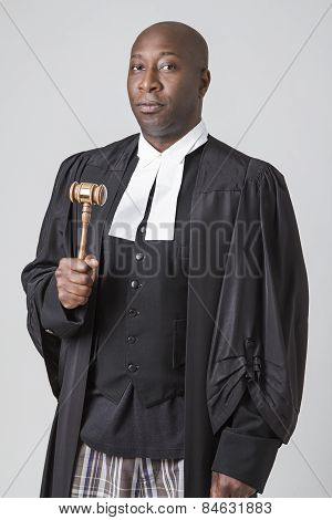 forty something bald african american wearing a canadian lawyer toga holding a gavel poster