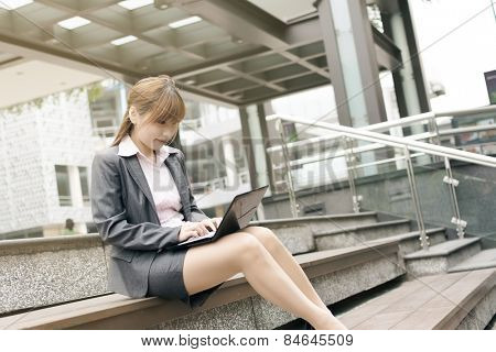 Attractive Asian business woman use laptop in outdoor street, shot at Xinyi business district, Taipei, Taiwan.